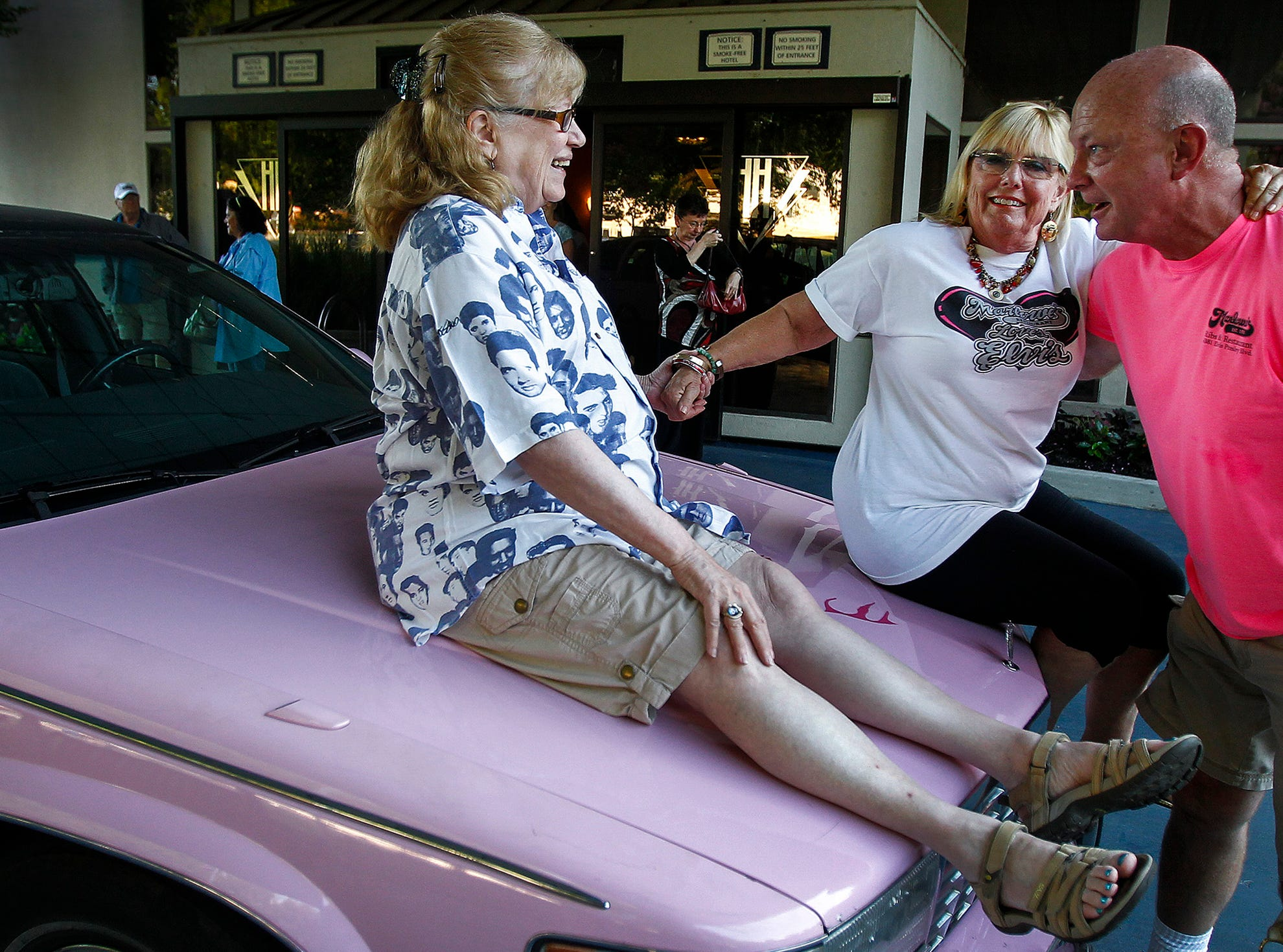 August 6, 2015 - Mary Hinds, from Los Angeles, (middle) gets a lift from Marlowe's driver Jim Deweese (right) to take a picture with longtime friend Marjorie Montgomery, of Boston, as they pose with a painted Elvis face on a pink limousine. The pair have been coming to Memphis for Elvis week for 23 years, and have a 4-page type-written list of places they try to eat when they're here. (Mark Weber/The Commercial Appeal)
