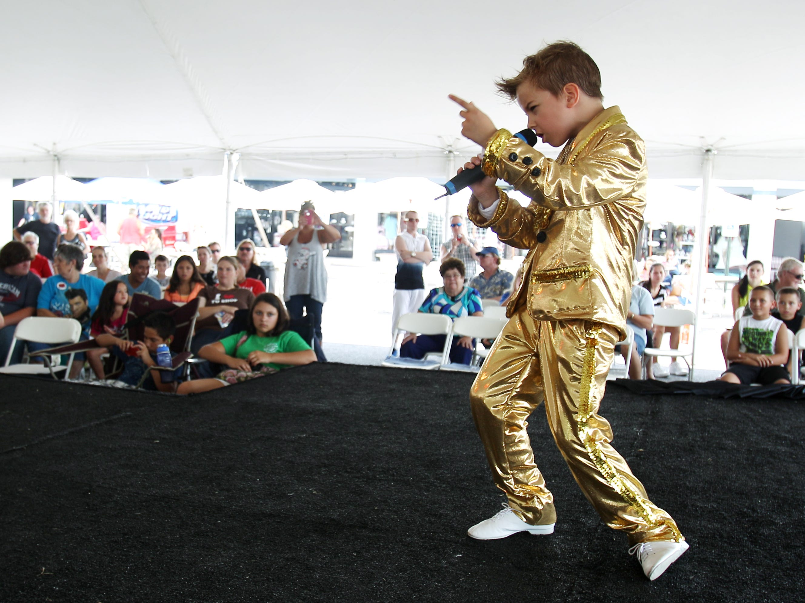August 11, 2014 - John Paul Melling, 8, of Manchester, England, sings karaoke at Graceland Crossing as part of Elvis Week festivities on Monday. (Mike Brown/The Commercial Appeal)