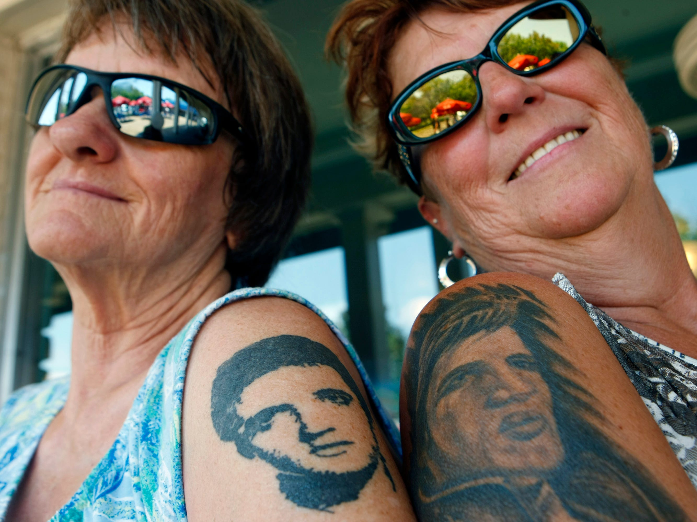 "August 9, 2013 - Mary Johnson and Sherry Martindale both have Elvis tattoos and the fans come every year for Elvis week. ""It is like a family reunion"" says Martindale, who has several more Elvis tattoos and she plans to get even more. Elvis fans began to gather in and around Memphis and Graceland for the official start of Elvis Week which begins Saturday. ( Karen Pulfer Focht/ The Commercial Appeal)"
