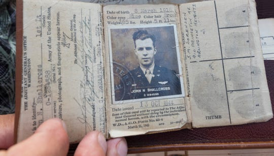 "Scott Schallcross holds his father's military papers from World War II at the EAA AirVenture in Oshkosh. His father was part of the crew that flew a C-47 named ""That's All, Brother""."