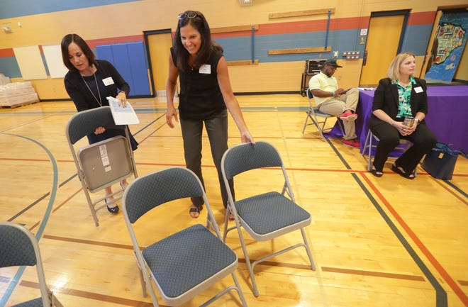 """Ann Leinfelder Grove, left, president and CEO of the SaintA social agency, helps Amy Lovell set up chairs during a July 2018 meeting of SWIM, """"Scaling Wellness in Milwaukee."""" The SWIM initiative is an effort to create strategic coordination in Milwaukee's disjointed trauma-responsive initiatives."""