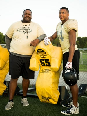 Mt. Juliet's Reggie Grimes II, right, poses for a portrait with his father, assistant coach Reggie Grimes, left, during practice at Mt. Juliet High School in Mt. Juliet, Tenn., Monday, July 23, 2018.