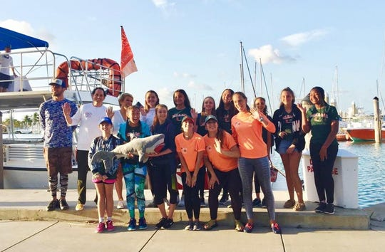 """Seacrest Country Day School sophomore Isabella Stapp, second from left in front row, was invited to join the University of Miami's shark research and conservation program on a shark tagging expedition that included Barbara Corcoran of reality TV """"Shark Tank."""""""