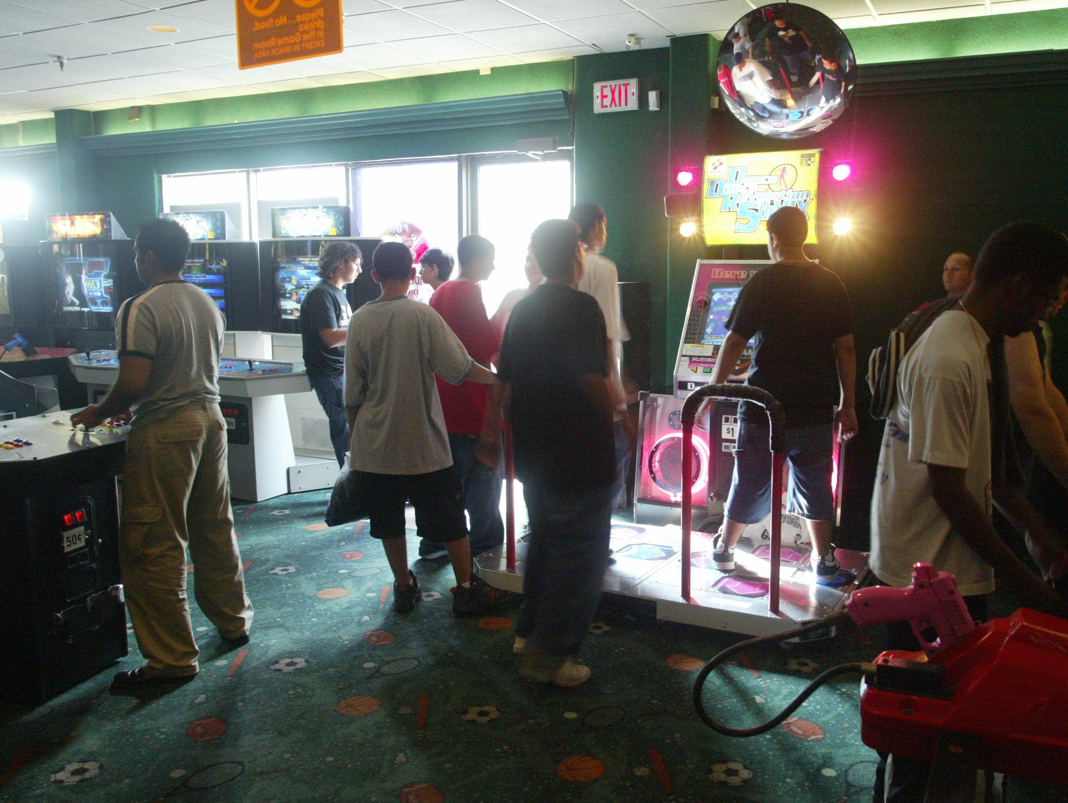 Players congregate around a Dance Dance Revolution machine at Fun N Games arcade in Wayne.