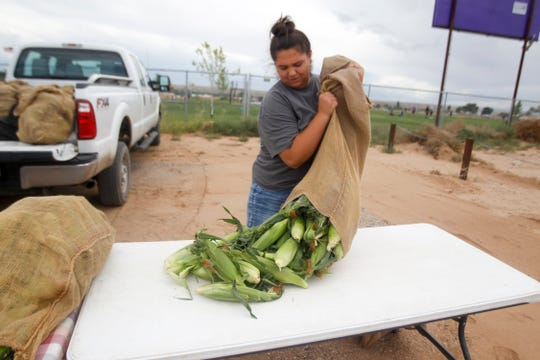 Hallie Sutherland, of Sutherland Farms, empties a sack of corn Monday as she sets up for the Kirtland Town Hall Growers Market.