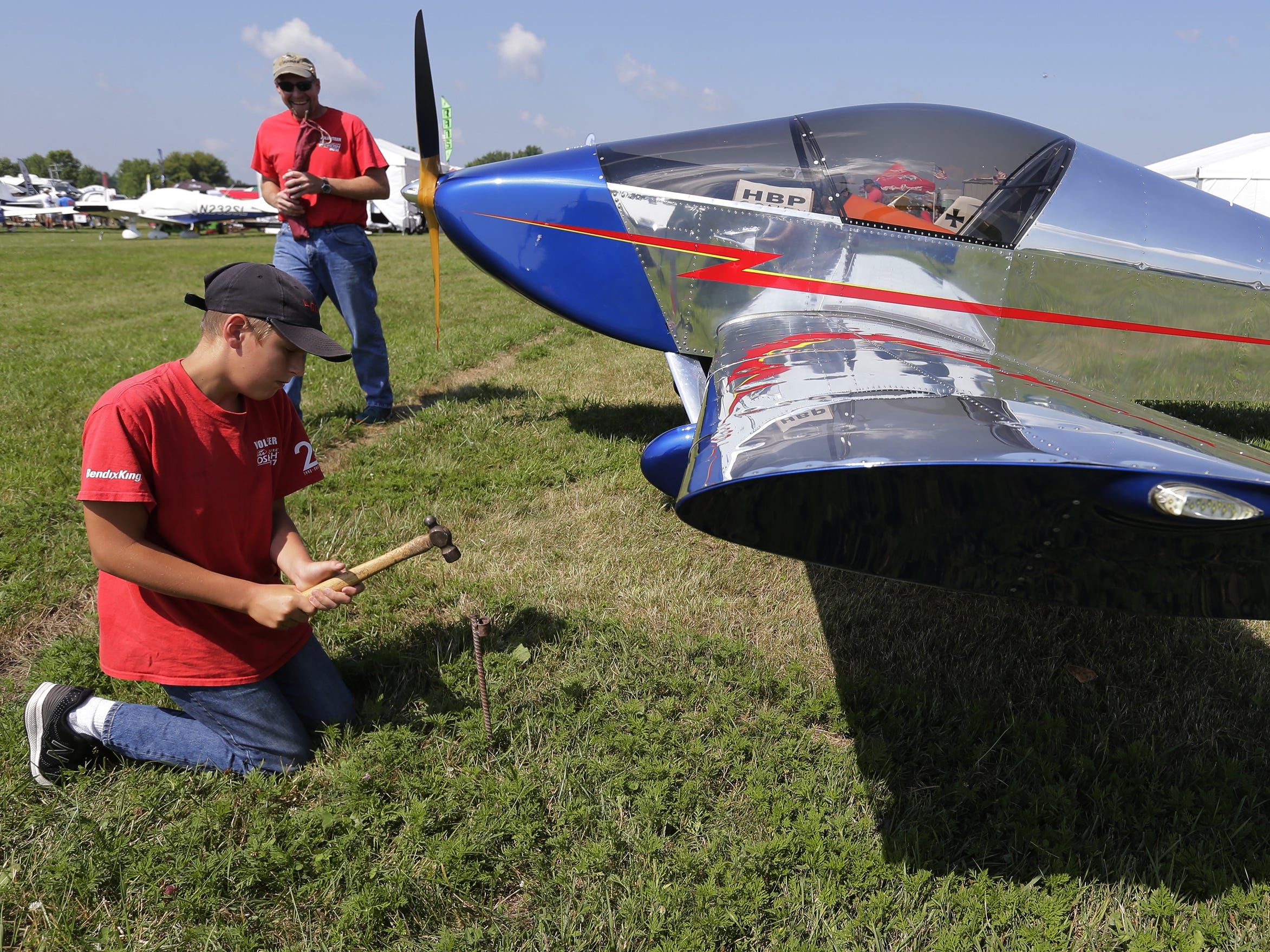 Frank Zuege pounds a stake into the ground as he helps his dad James Zuege of Kewanee, Wis., tie off their SONEX that they flew to Oshkosh Tuesday, July 24, 2018, in Oshkosh, Wis.  The 66th annual Experimental Aircraft Association Fly-In Convention, AirVenture 2018 draws over 500,000 people annually to the area.  The convention runs through July 29. Joe Sienkiewicz/USA Today NETWORK-Wisconsin