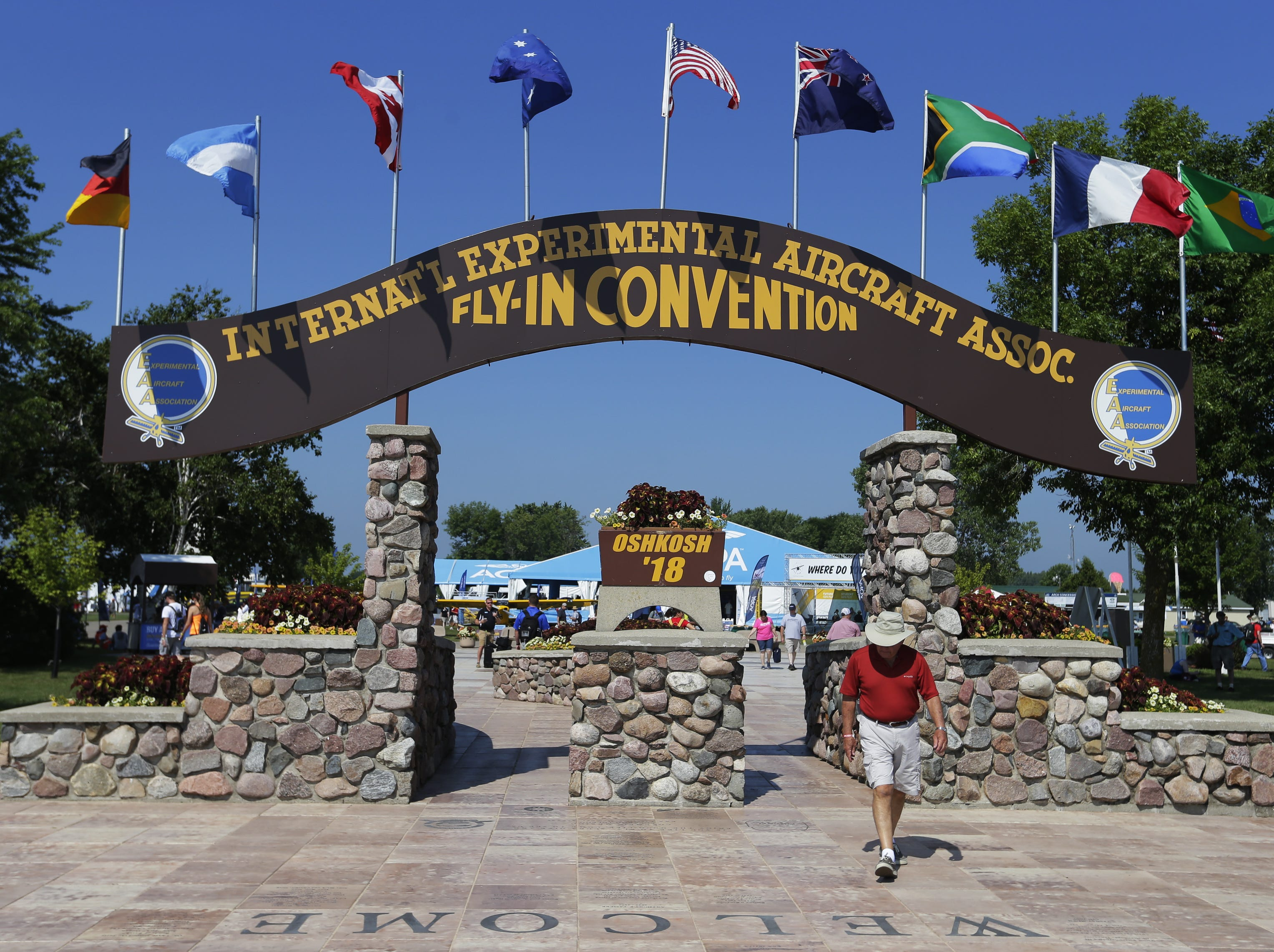 The Fly-In Convention arch is an icon as people pass to get to the flightline,Tuesday, July 24, 2018, in Oshkosh, Wis.  The 66th annual Experimental Aircraft Association Fly-In Convention, AirVenture 2018 draws over 500,000 people annually to the area.  The convention runs through July 29. Joe Sienkiewicz/USA Today NETWORK-Wisconsin