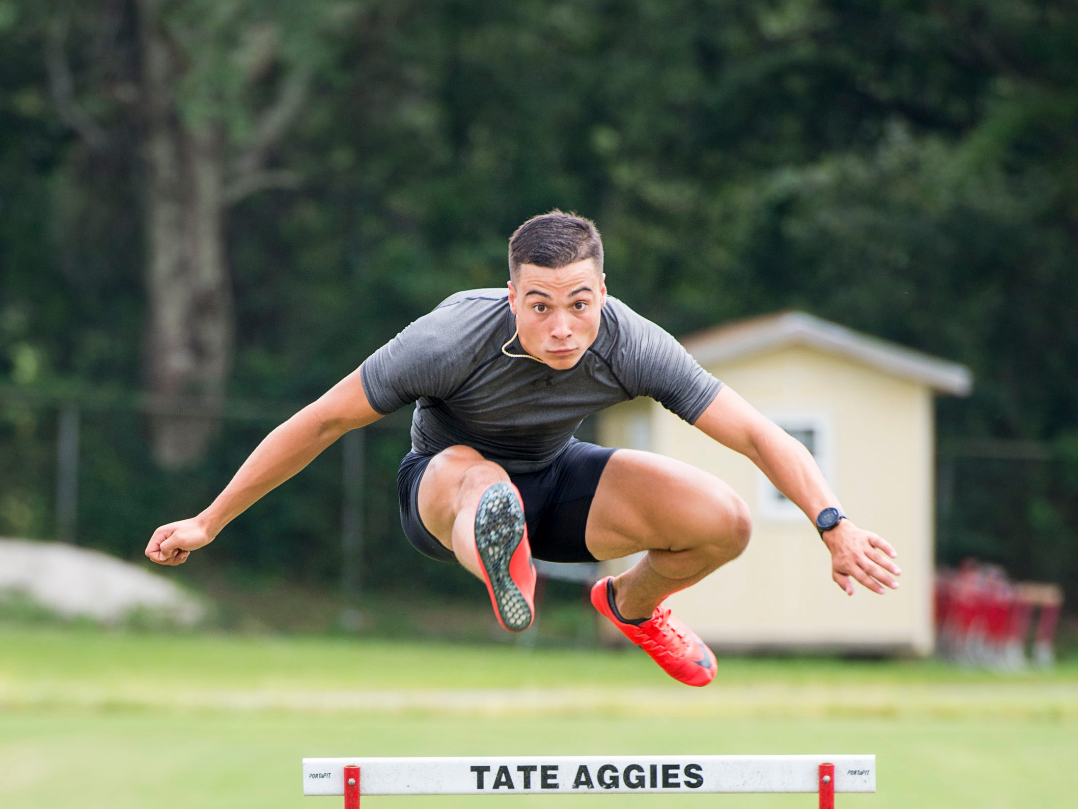 Decathlete Joseph Zayszly shows his hurdling technique at Tate High School in Pensacola on Tuesday, July 24, 2018.