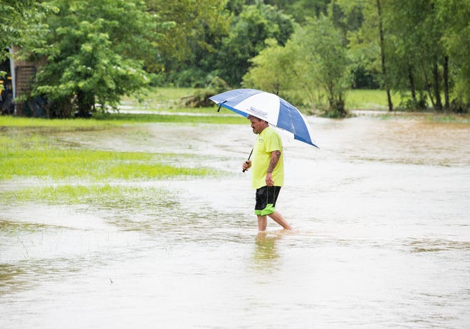 Ken Kelbaugh walks through flood waters coming from the West Branch of Codorus Creek after checking on his property and clearing debris on July 24, 2018.