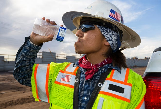 Foreman James Arthur takes a water break at the South Mountain Freeway construction site near 59th Ave. south of Van Buren Street on July 24, 2018, in Phoenix, Ariz.