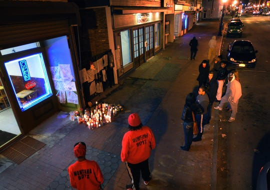In this Dec. 24, 2012 file photo, people gather to light candles and to pay respect to Daquell LeBlanc, 17, where he was killed on Main Street in the City of Poughkeepsie.