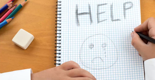 An image /poster covering the Social Issues of child abuse, schoolchild in uniform at a desk asking for help by a written message saying Help with a sad face .