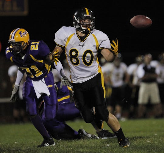 East's Calvin Bain runs next to McQuaid's Brian Parker, who waits for the ball, in the second quarter at East-High School on Sept. 5, 2009.