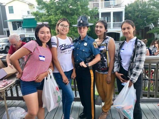 Delaware State Police Trooper Irina Celpan poses with a group of J-1 students.