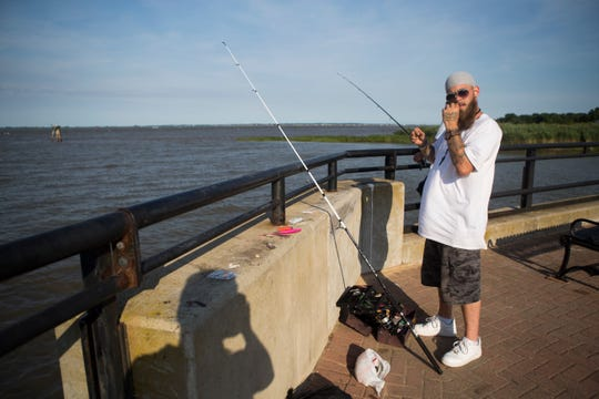 "Paul Daniels Jr. fishes at the Delaware City waterfront Tuesday, June 26, 2018. Daniels Jr. is unsure if rapid growth would be good for Delaware City. ""Everyone here is so friendly,"" Daniels said. ""If this gets built up like Middletown, that won't happen anymore."""