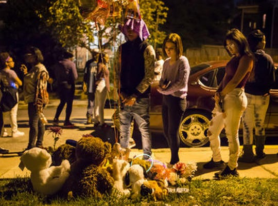 "Friends of Keshall ""KeKe"" Anderson look at stuffed animals and balloons left near the spot where she was killed along W. 20th Street in Wilmington at a vigil commemorating her 20th birthday in October 2016."
