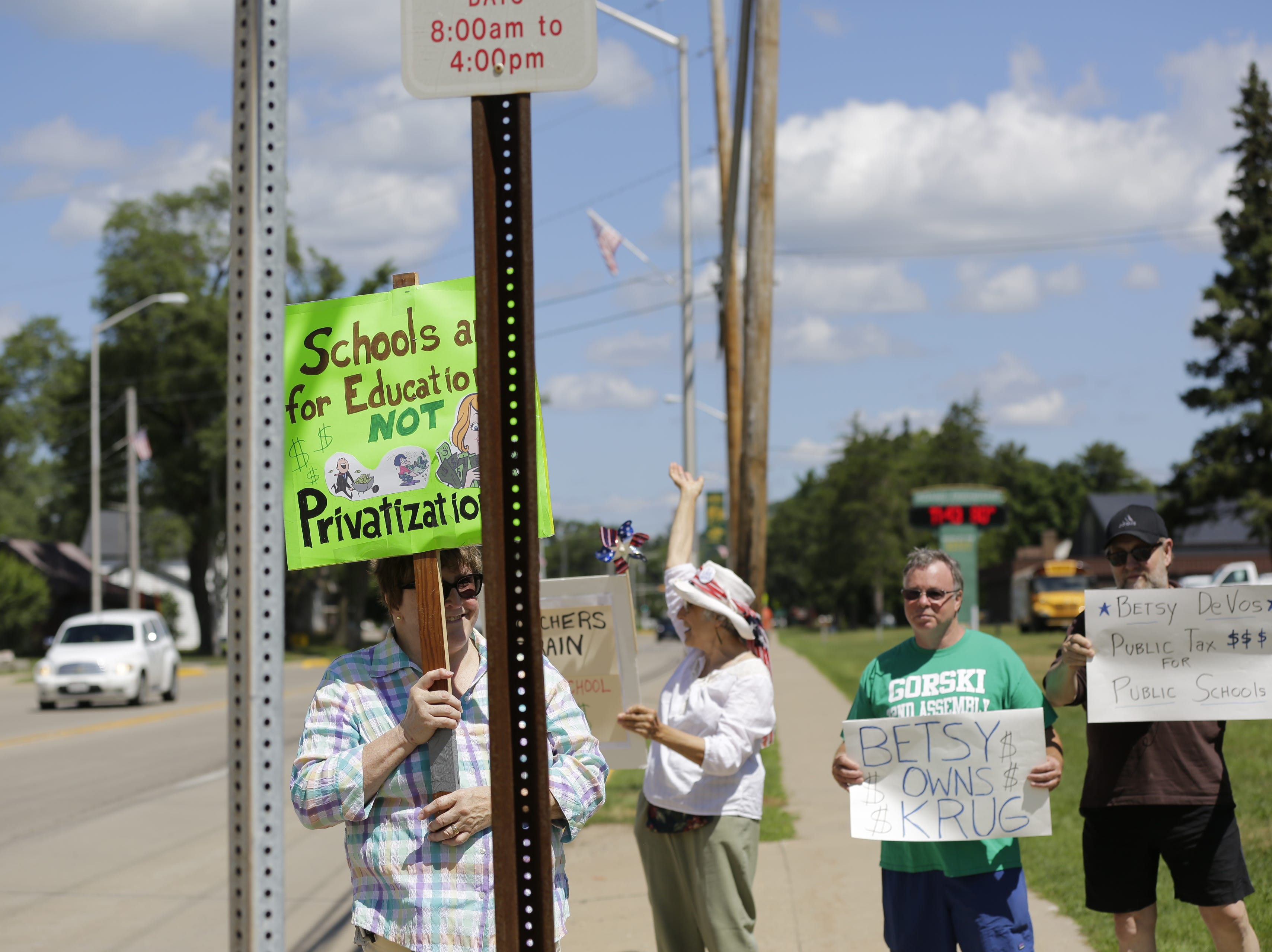Protestors Lou Ann Schmitz, left, Arlene Kanno, David Gorski, democratic candidate for Wisconsin's 72nd assembly district and Kevin Stellman, stand along North Main Street in front of Adams-Friendship Middle School in Adams, Wis. as U.S. Secretary of Education Betsy DeVos appears at the school Tuesday, July 24, 2018.