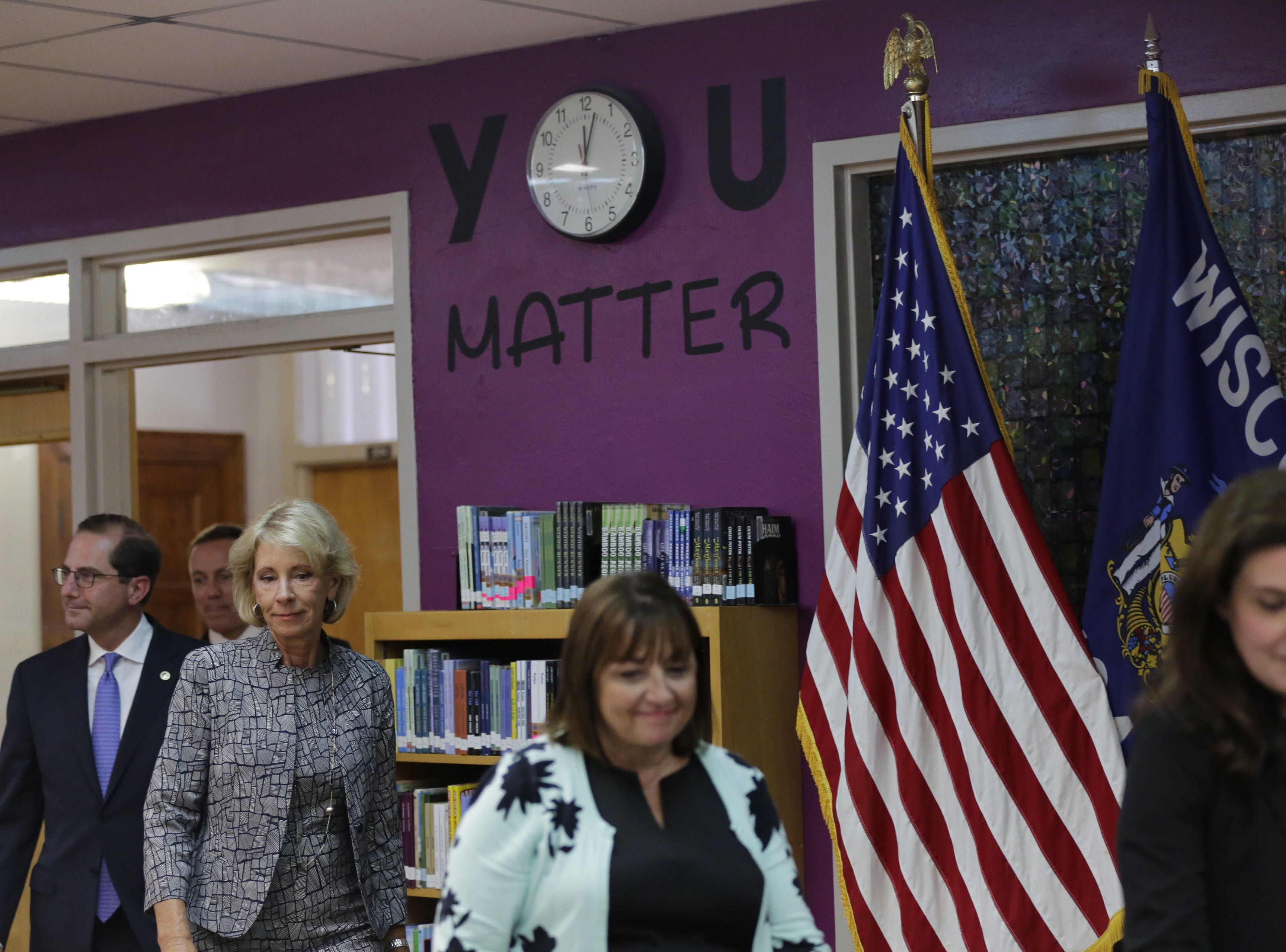 U.S. Secretary of Education Betsy DeVos, center, enters the library of Adams-Friendship Middle School in Adams, Wis. with Wisconsin first lady Tonette Walker, right and U.S. Health and Human Services Secretary Alex Azar, left Tuesday, July 24, 2018.