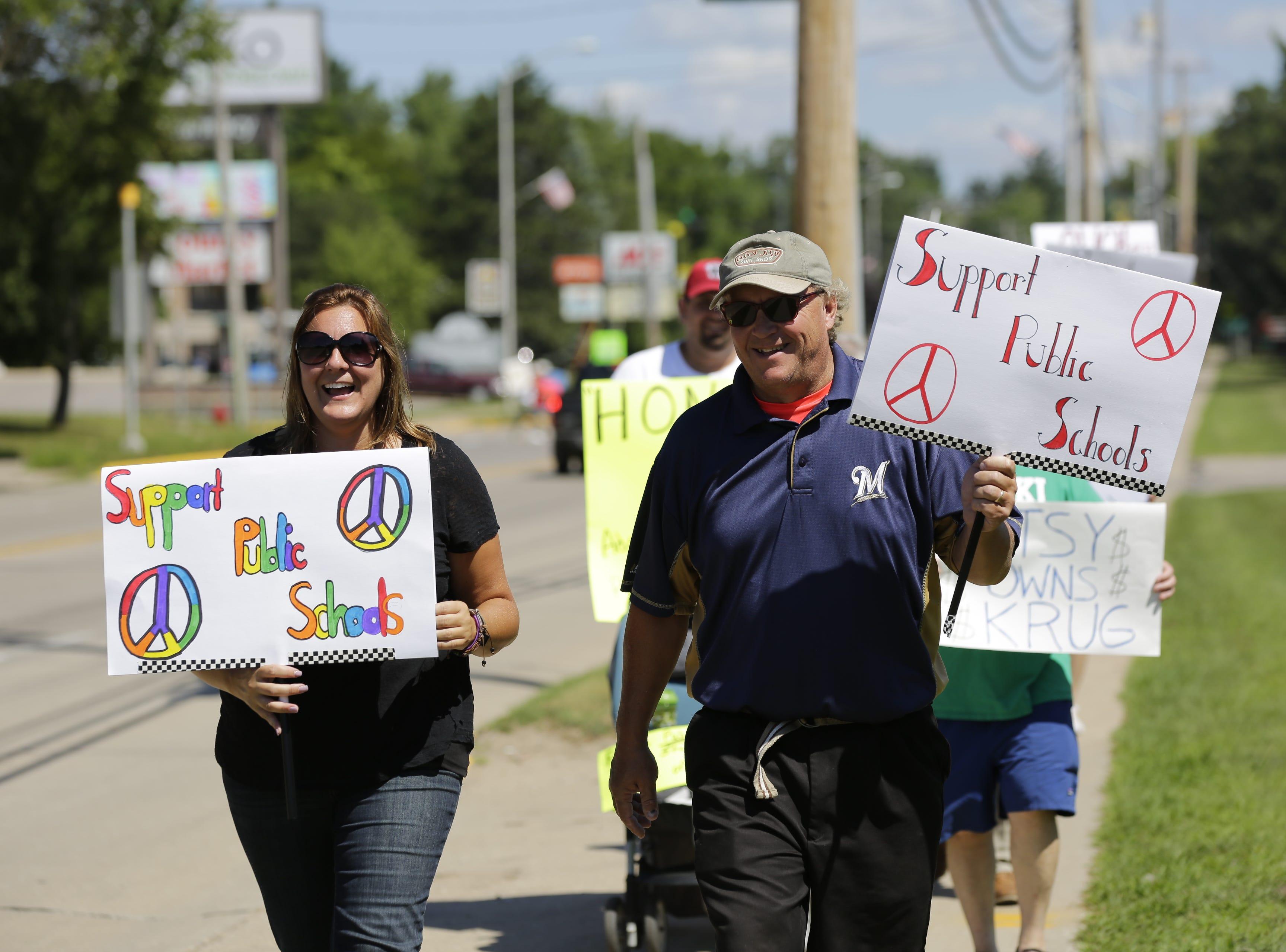 Protestors Jennie Moore and Andy Kloff walk along North Main Street in front of Adams-Friendship Middle School in Adams, Wis. as U.S. Secretary of Education Betsy DeVos appears at the school Tuesday, July 24, 2018.