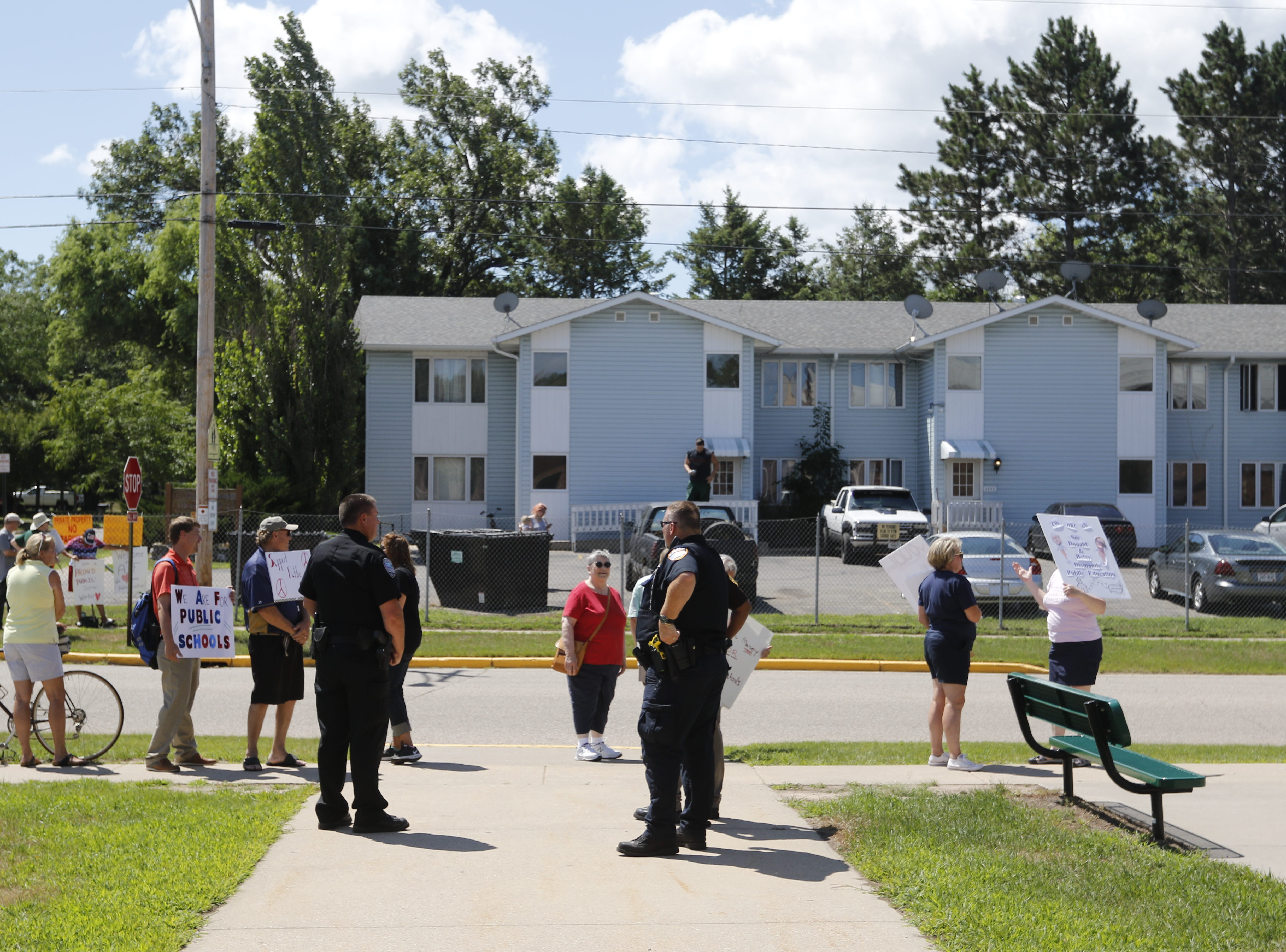 Protestors and police stand along East Brevoort Street in front of Adams-Friendship Middle School in Adams, Wis. as U.S. Secretary of Education Betsy DeVos appears at the school Tuesday, July 24, 2018.
