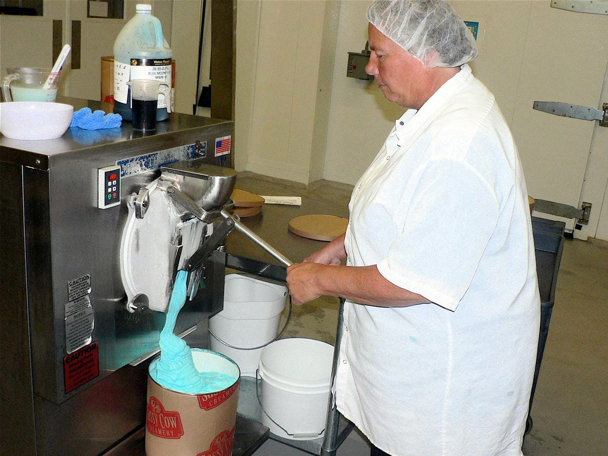 Brenda Brace, ice cream manager, handfills a three gallon container with Blue Moon ice cream.