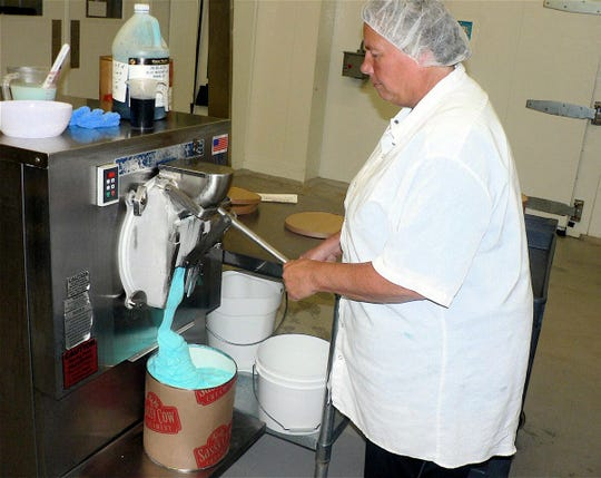 Brenda Brace, ice cream manager, handfills a three gallon container with Blue Moon ice cream.