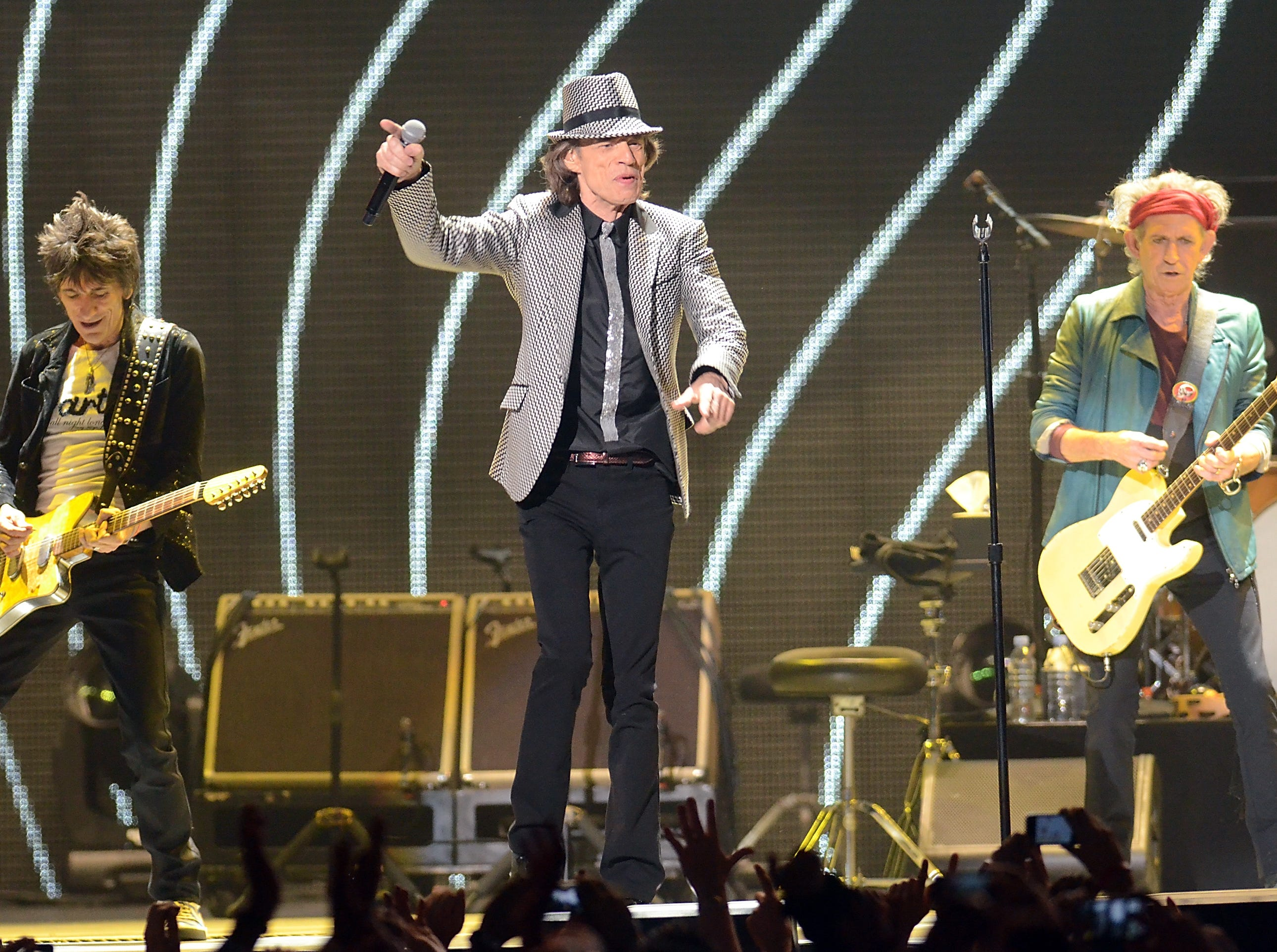 In this Saturday, Dec. 15, 2012 file photo, singer Mick Jagger, center, guitarists Ronnie Wood, left, and Keith Richards, of The Rolling Stones perform live at the Prudential Center in Newark, N.J.  (Photo by Evan Agostini/Invision/AP, File) ORG XMIT: CAENT418