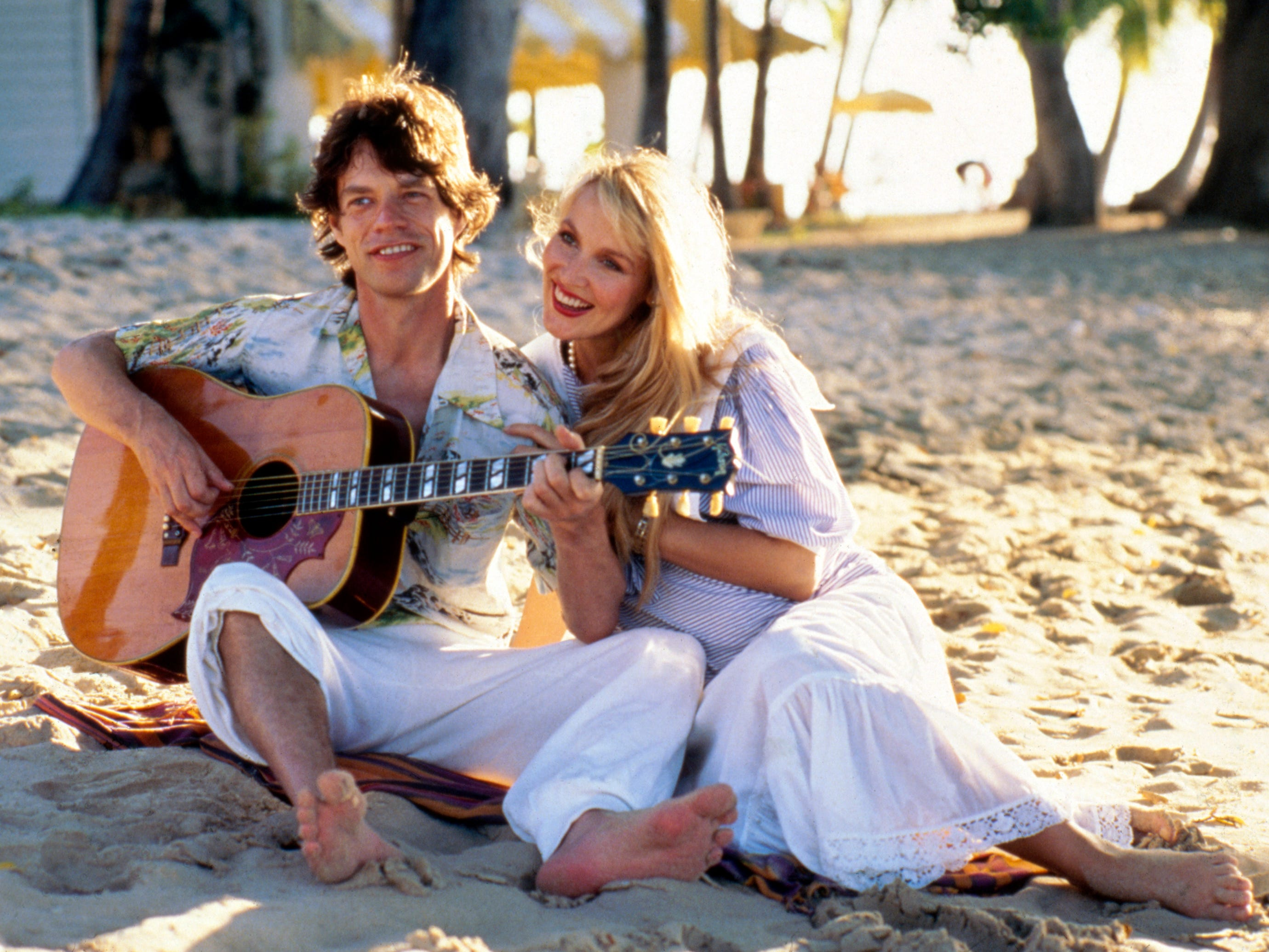 British rock musician Mick Jagger from The Rolling Stones, with his fiancee Jerry Hall at Gibbs Beach, St. Peter, Barbados on Dec. 5, 1983. (AP Photo/Paul Benoit)