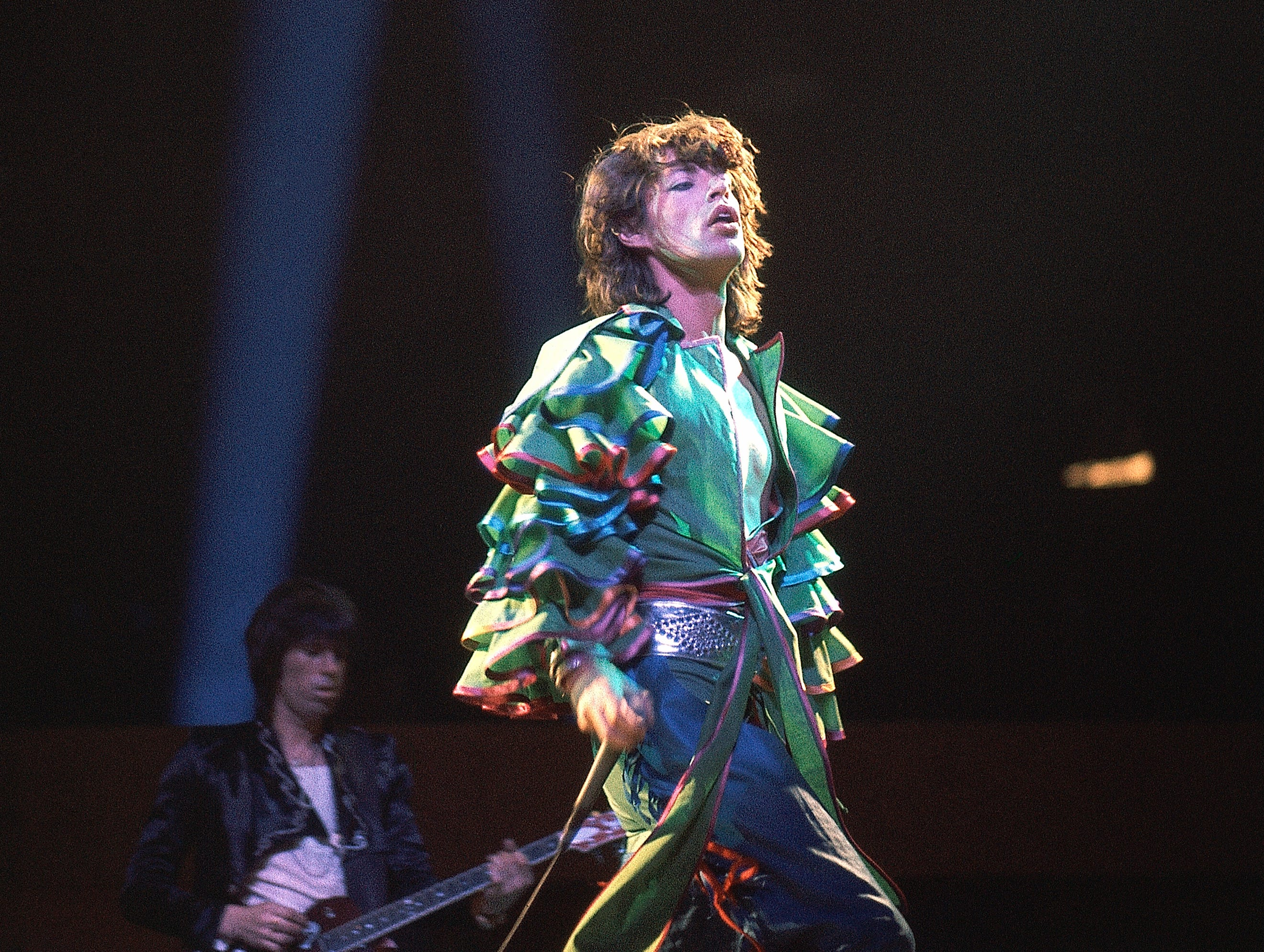 Mick Jagger singing in The Rolling Stones at the Frankfurt concert hall, Germany around April 28, 1976 where the famous British rook group started their longest ever concert tour, leading them round the globe. The European leg of their tour ends on June 23 in Vienna. Keith Richards can be seen playing the drums in behind. (AP Photo)