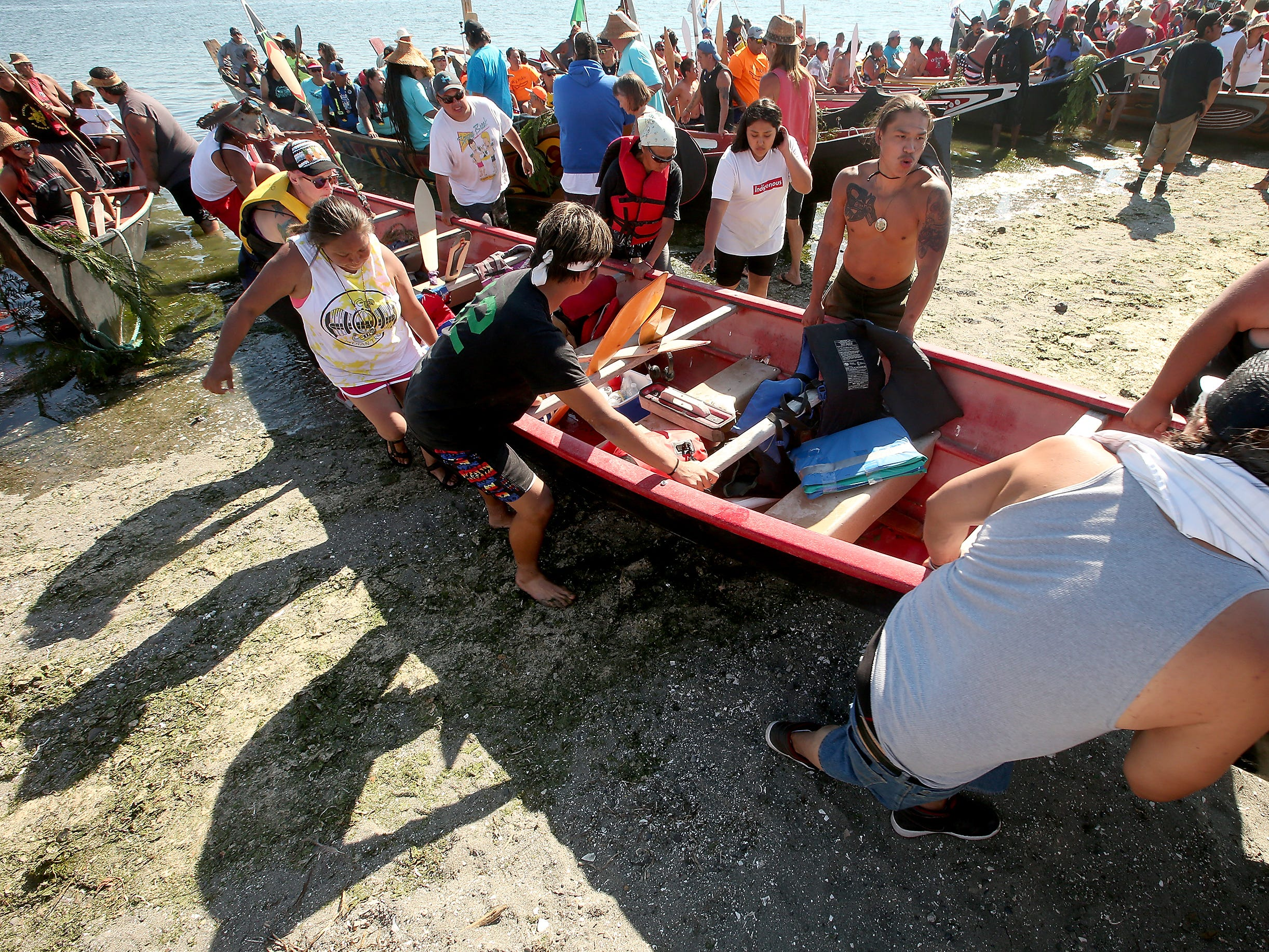 """Canoes are carried further up the beach after the Tribal Canoe Journey """"Paddle to Puyallup"""" landed at Point Julia on Tuesday, July 24, 2018."""
