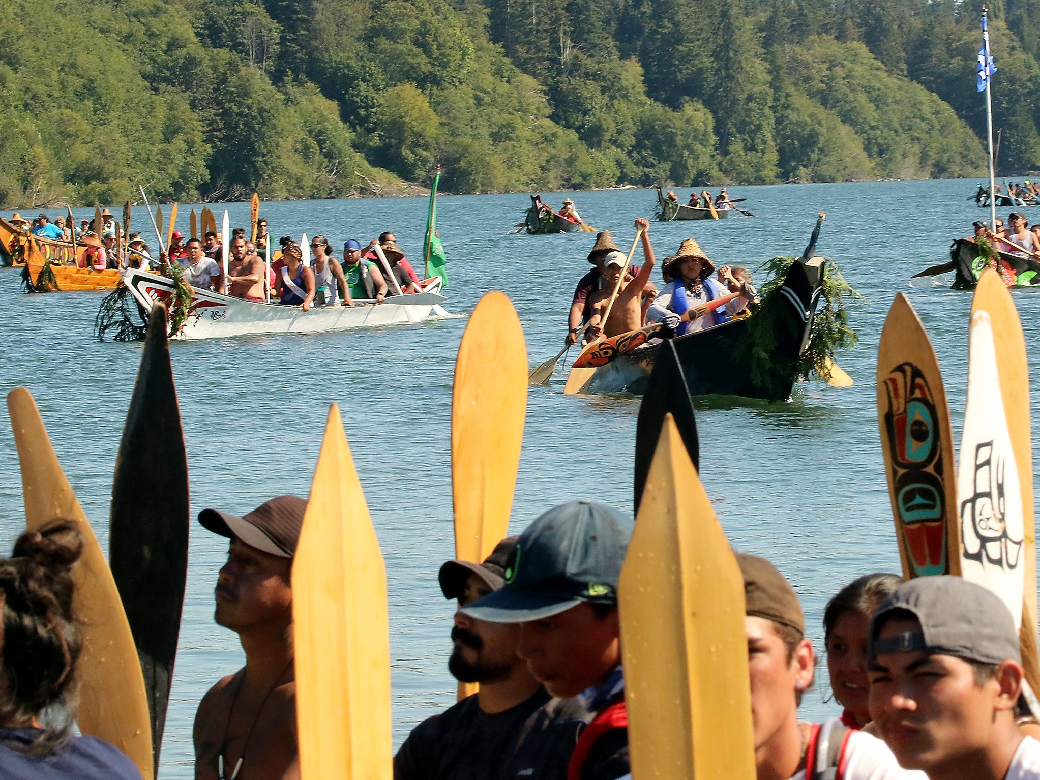 """Tribal Canoe Journey """"Paddle to Puyallup"""" canoes head for the shore to ask and await permission from the Port Gamble S'Klallam Tribe to come ashore at Point Julia on Tuesday, July 24, 2018."""