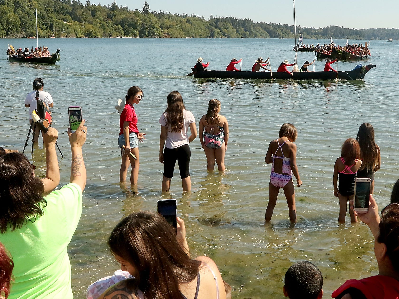 """Tribal Canoe Journey """"Paddle to Puyallup"""" canoes parade past those on shore of Point Julia on Tuesday, July 24, 2018."""