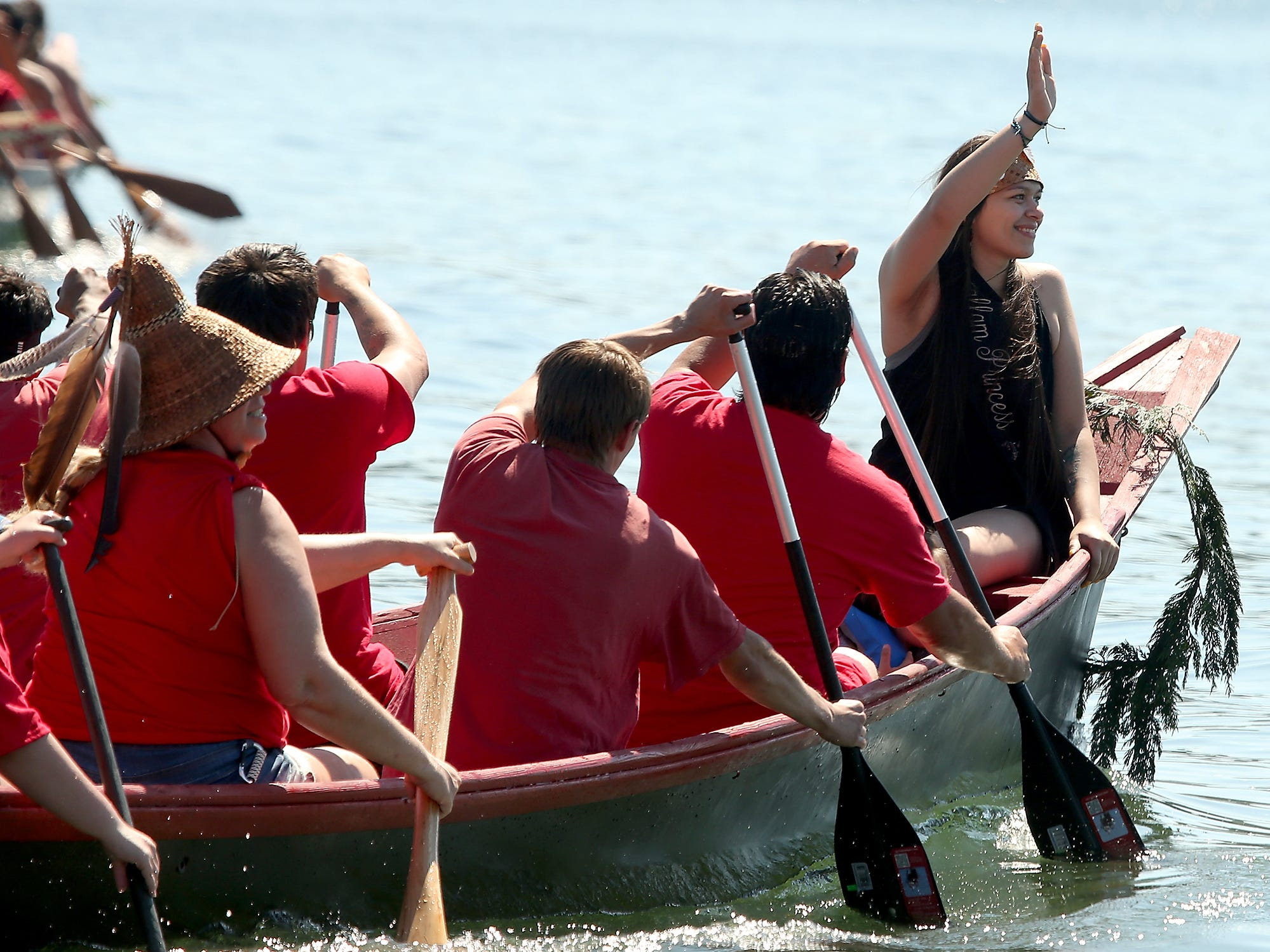 """Senior Miss S'Klallam Days Karleigh Gomez waves to those on shore as the Tribal Canoe Journey """"Paddle to Puyallup"""" lands at Point Julia on Tuesday, July 24, 2018."""