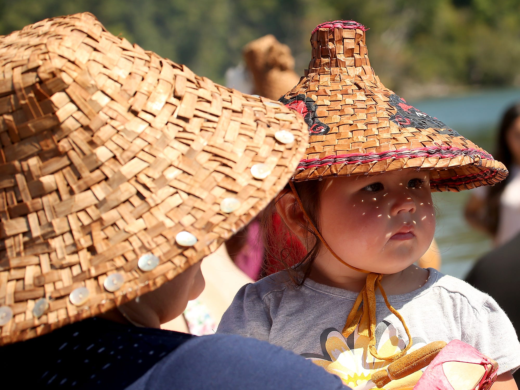 Dapples by the sunshine through her hat, Emma Marquez, 4, a member of the Lower Elwha Klallam Tribe, watches as the canoes head for the shore during the Tribal Canoe Journey ÒPaddle to PuyallupÓ landing at Point Julia on Tuesday, July 24, 2018.