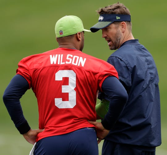 New Seahawks offensive coordinator Brian Schottenheimer goes over the offense with Russell Wilson during a practice session last month in Renton.