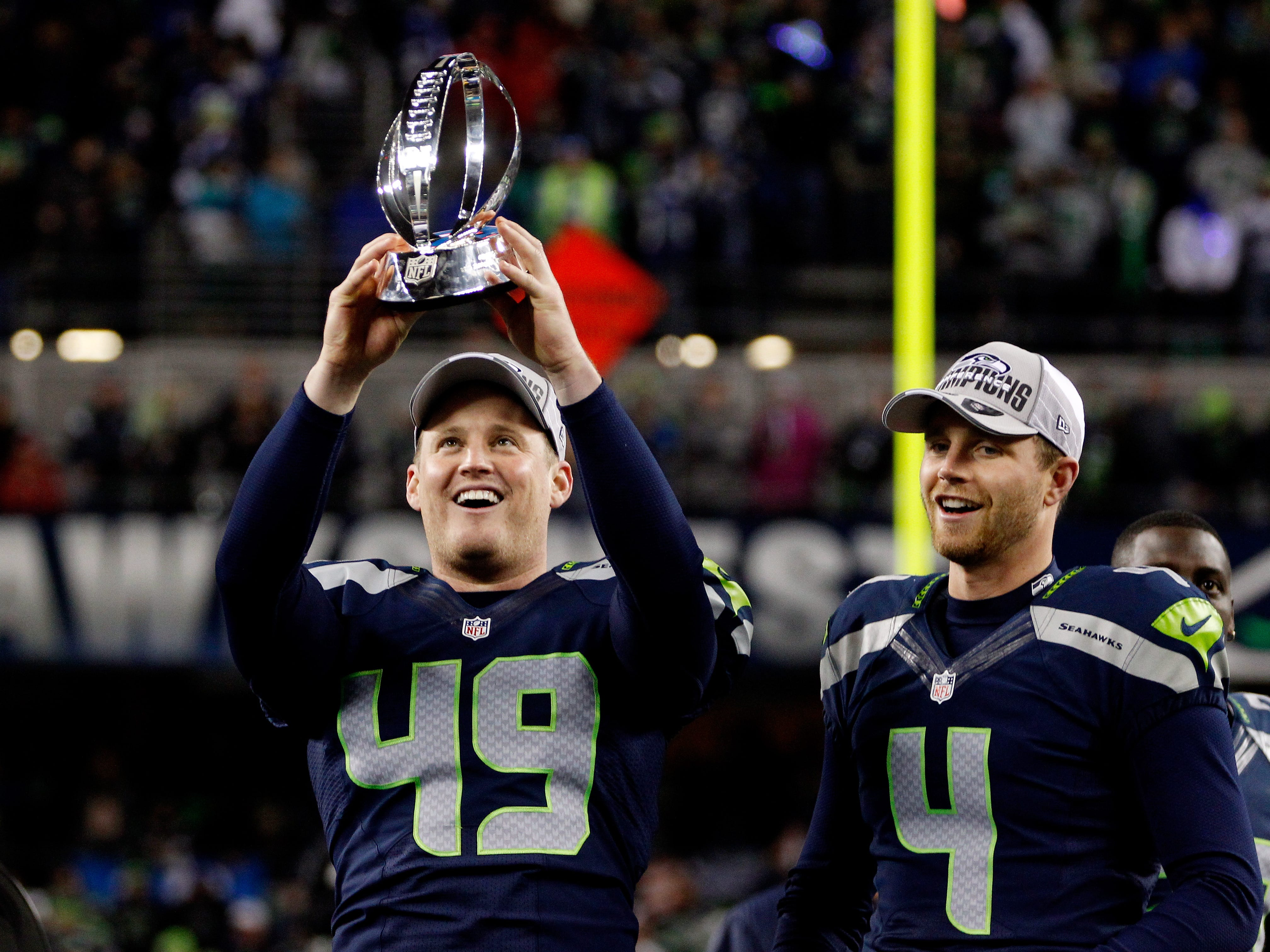 Clint Gresham #49 and kicker Steven Hauschka #4 of the Seattle Seahawks celebrate with the George Halas Trophy after the Seahawks 23-17 victory against the San Francisco 49ers during the 2014 NFC Championship at CenturyLink Field on January 19, 2014 in Seattle, Washington.  (Photo by Otto Greule Jr/Getty Images)