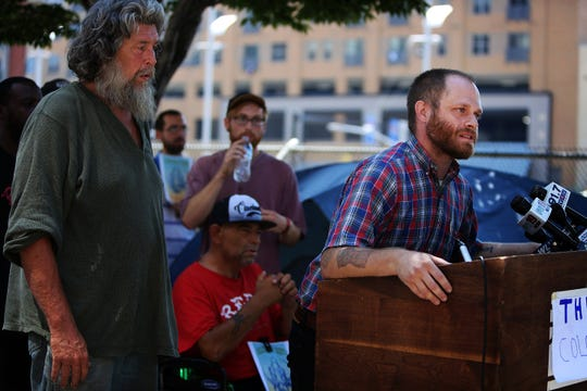 Josh Spring, executive director of the Cincinnati Homeless Coalition speaks during a press conference held on Third Street, where a group of homeless people have been placing their tents. A homeless camp beneath the Interstate 71 overpass near Third Street was recently cleared out.