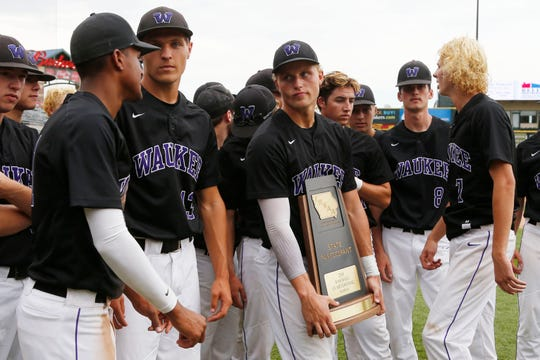 Waukee players hold their state tournament participant trophy Wednesday, July 25, 2018, after their quarterfinal loss to West Des Moines Valley at the state baseball tournament in Des Moines.