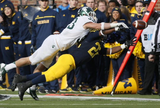 Michigan State's Jon Reschke, top, breaks up a pass to Michigan's Karan Higdon in the second quarter on Saturday, Oct. 17, 2015, at Michigan Stadium in Ann Arbor.