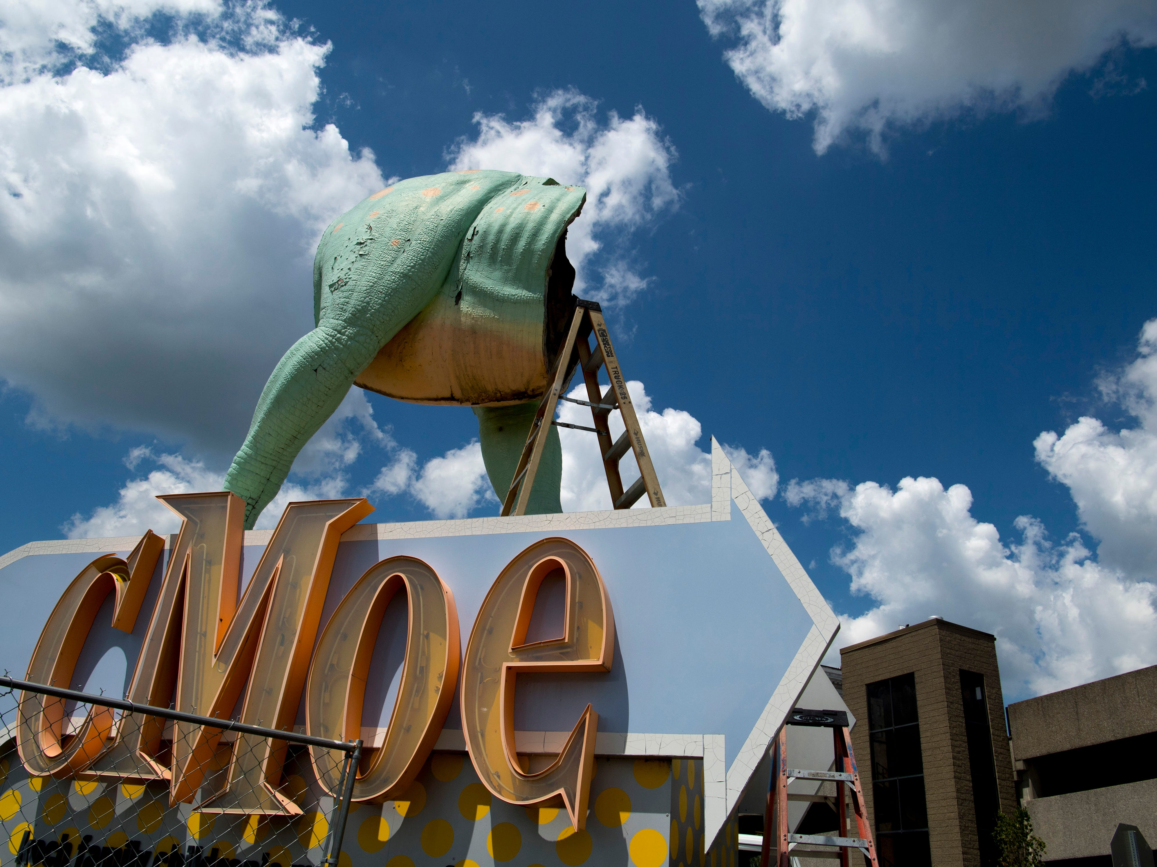 A headless and tailless Millie spends her last minutes perched across from the Koch Family Children's Museum of Evansville Wednesday morning. She was later transported to Custom Sign in Newburgh, Ind., for restoration. The new construction at her corner of Locust and Fifth streets is forcing her to find a new place to call home.