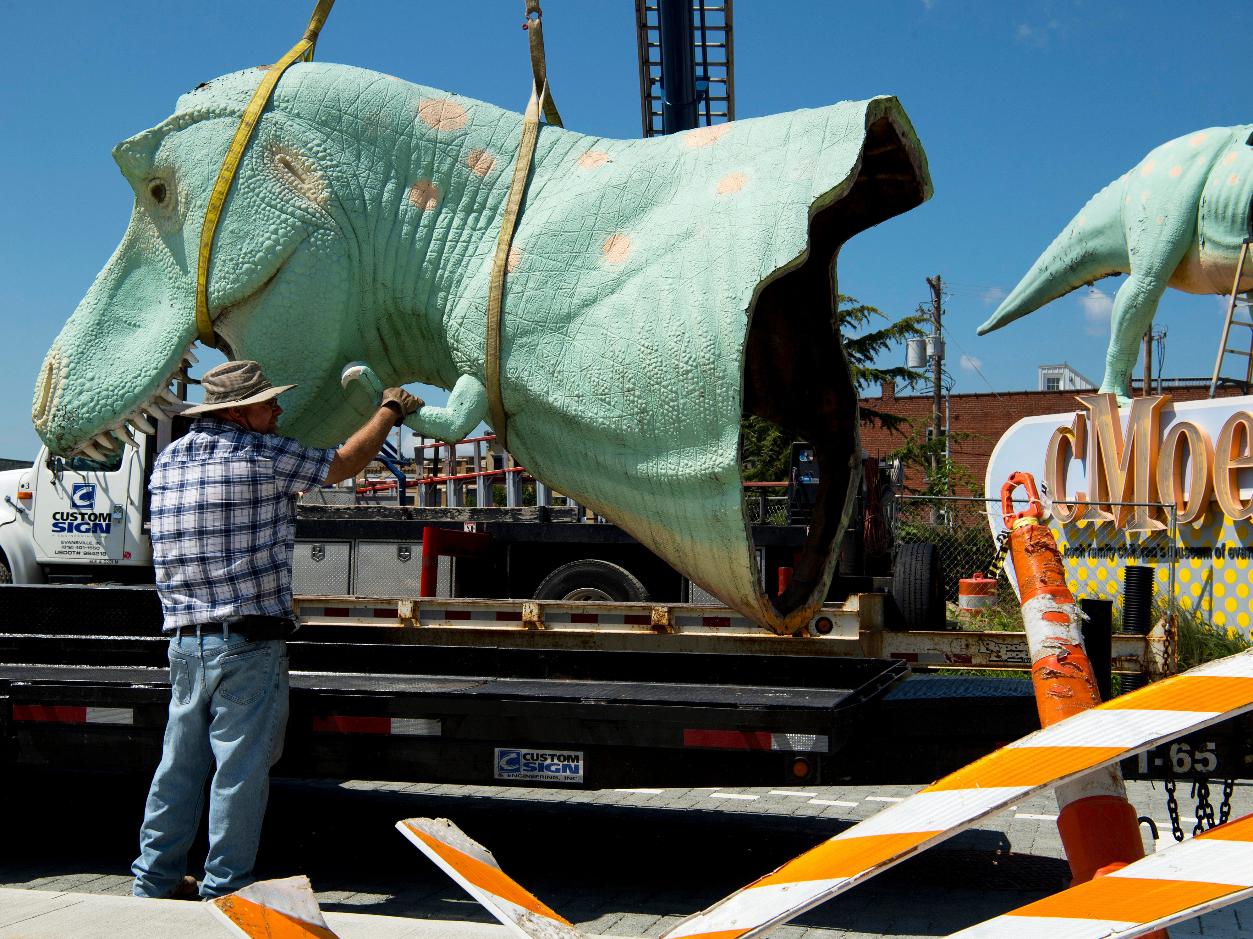 Jay Pipken with Custom Sign of Newburgh, Ind., holds the tiny arm of Millie, a Tyrannosaurus Rex dinosaur – and the Koch Family Children's Museum of Evansville's most recognizable face – as she is placed on a trailer Wednesday morning. Millie has perched atop her pedestal at the corner of Locust and Fifth streets for more than a decade and is getting a new paint job. It is unknown where the green T-Rex will reside after her facelift, but cMoe assures us Millie's new home will be easily seen in the Downtown Evansville area.