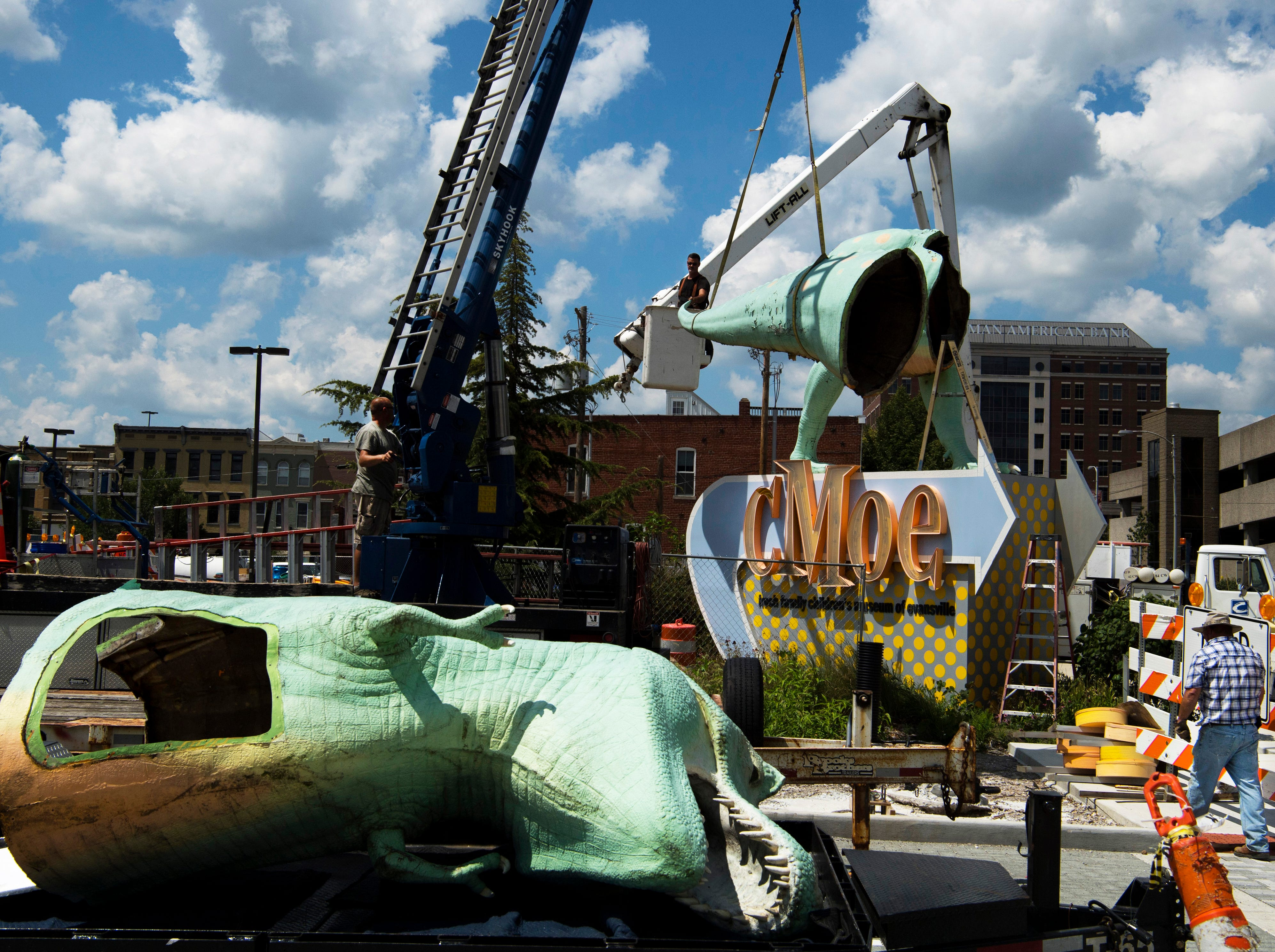 Millie, a Tyrannosaurus Rex dinosaur – and the Koch Family Children's Museum of Evansville's most recognizable face – is disassembled by Bart Meyer, top center, and the team from Custom Sign of Newburgh, Ind., Wednesday morning. Millie has perched atop her pedestal at the corner of Locust and Fifth streets for more than a decade and is getting a new paint job. It is unknown where the green T-Rex will reside after her facelift, but cMoe assures us Millie's new home will be easily seen in the Downtown Evansville area.
