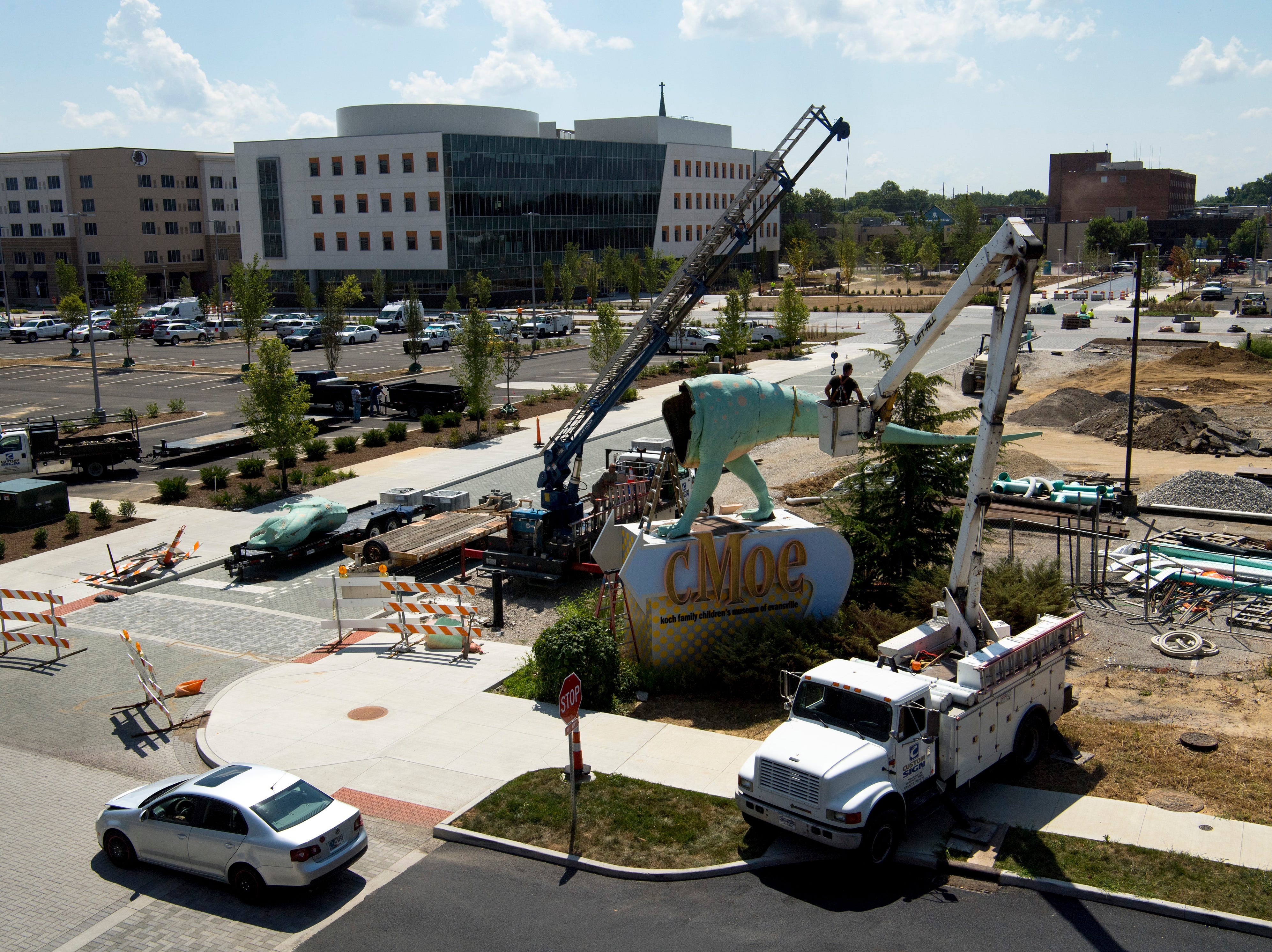 Millie, a Tyrannosaurus Rex dinosaur – and the Koch Family Children's Museum of Evansville's most recognizable face – is disassembled by the team from Custom Sign of Newburgh, Ind., Wednesday morning. Millie has perched atop her pedestal at the corner of Locust and Fifth streets for more than a decade and is getting a new paint job. It is unknown where the green T-Rex will reside after her facelift, but cMoe assures us Millie's new home will be easily seen in the Downtown Evansville area.
