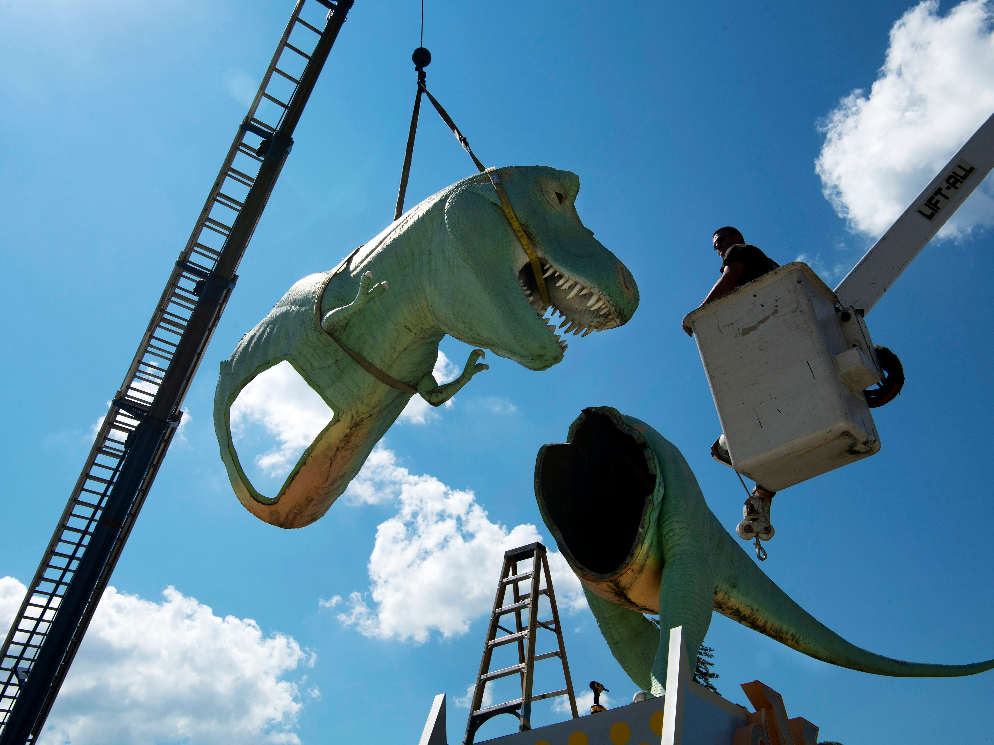 Millie, a Tyrannosaurus Rex dinosaur – and the Koch Family Children's Museum of Evansville's most recognizable face – is disassembled by Bart Meyer, right, and the team from Custom Sign of Newburgh, Ind., Wednesday morning. Millie has perched atop her pedestal at the corner of Locust and Fifth streets for more than a decade and is getting a new paint job. It is unknown where the green T-Rex will reside after her facelift, but cMoe assures us Millie's new home will be easily seen in the Downtown Evansville area.