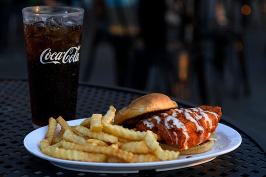 The Bina's Buffalo Chicken Sandwich at The Rooftop Food & Drinks features fried chicken covered in a house-made Buffalo sauce dressed with lettuce, tomato, pickle and onion and a side of fries.