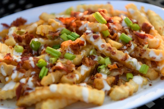 A featured starter item at The Rooftop Food & Drinks is the loaded fries which are topped with bacon, chives, ranch and Queso.
