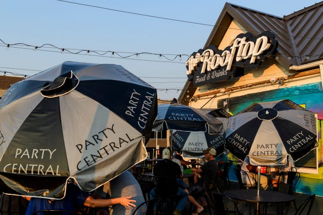 People enjoy cool weather while eating dinner on the rooftop patio at Rooftop Food & Drinks.