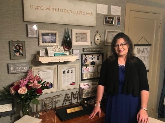 """Lydia Riley stands by her """"Wall of Faith"""" above the desk from which she runs a nationwide Avon business from her home in Greenville."""