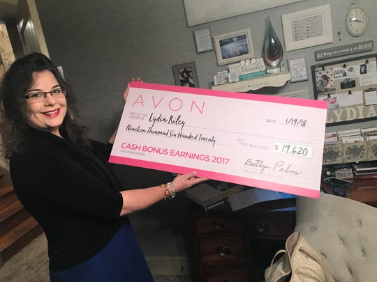 Lydia Riley holds a giant check for bonuses that earned her a national award from Avon.