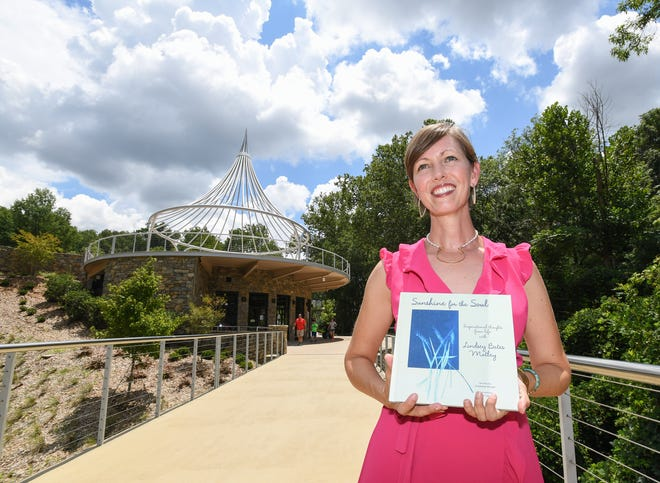 Stephanie Morgan stands on the bridge at the Cancer Survivors Park in downtown Greenville Wednesday, July 25, 2018 while holding the book she wrote, Sunshine for the Sole, that honors Lindsey Bates Motley who died of colon cancer.
